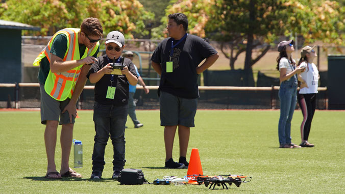 Man teaching boy about operating a drone