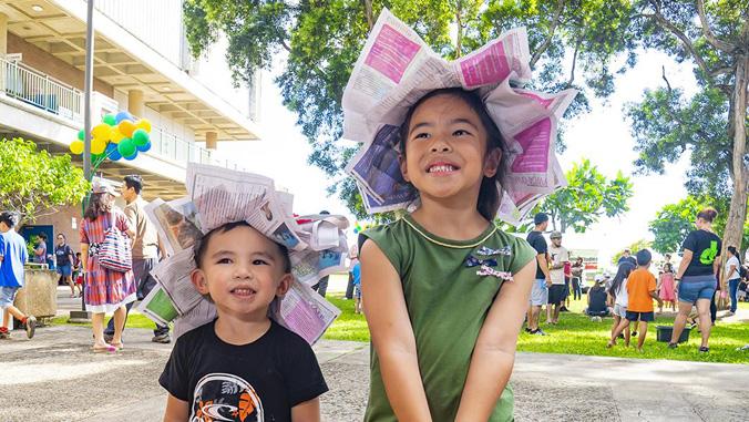kids wearing newspaper hats