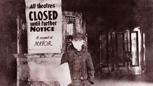 man next to closed theatre sign during 1918 flu