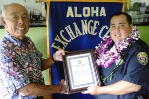 """Hilo Exchange Club Board Member Joey Estrella presents an """"Officer of the Month"""" for February plaque to Officer Luke Watkins."""
