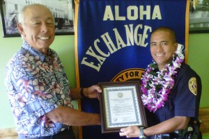 """Hilo Exchange Club Board Member Joey Estrella presents an """"Officer of the Month"""" for March plaque to Officer Keith Nacis."""
