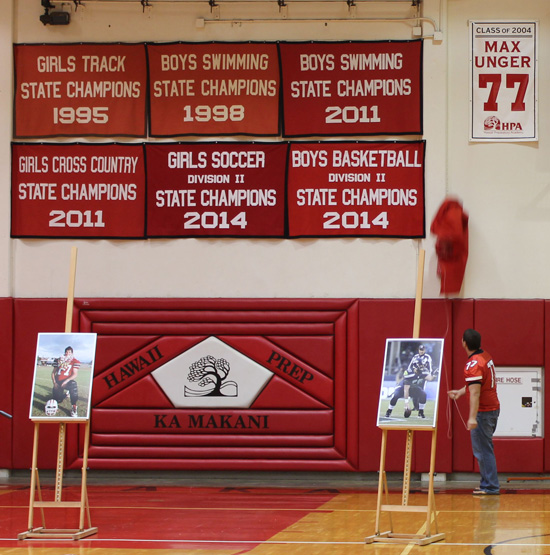 Keenan Greenbaum unveils the banner marking the retirement of No. 77. (Hawaii 24/7 photo by Karin Stanton)