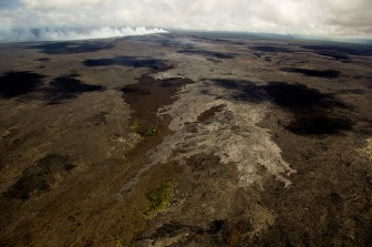 The episode 61g flow from Puʻu ʻŌʻō continues advancing downslope. In this photo, the current flow is the lighter color area along the center of the image. The flow front has advanced about 770 m (0.5 miles) since the June 16 overflight, which equates to an advance rate of about 100 m per day (330 ft per day). The flow front was roughly 100 m (330 ft) from the northern boundary of the abandoned Royal Gardens subdivision. Puʻu ʻŌʻō, and its plume, are visible near the top of the image. Photo taken Thursday, June 23, 2016 courtesy of USGS/HVO