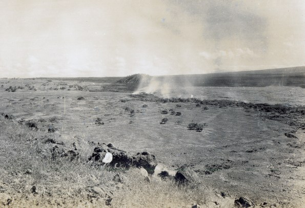 This photo, taken by Thomas Jaggar on December 21 during the1935 Mauna Loa eruption, shows the Humuula pāhoehoe flow ponding and slowly expanding eastward. The image looks east-southeast toward Puʻuhuluhulu from the southernmost Omaokoili cinder cone in the vicinity of today's Saddle Road and Mauna Kea Access Road juncture. USGS photo.