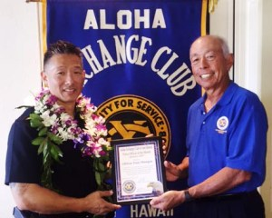 Aloha Exchange board member Joey Estrella presents an 'Officer of the Month' award to Officer Paul Mangus.