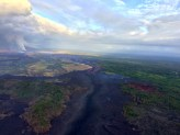 Aerial view of the fissure 8 lava channel on Kīlauea Volcano's lower East Rift Zone in the vicinity of the Kapoho cone, with fissure 8 fountains visible in the distance (upper left). Helicopter overflights of the eruption site are routinely scheduled to check for any new outbreaks of lava and to collect GPS data on the active flow—information that's needed to make the flow field maps that are posted on HVO's website (https://volcanoes.usgs.gov/volcanoes/kilauea/multimedia_maps.html).
