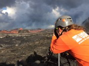 USGS Hawaiian Volcano Observatory geology field crews maintain watch over the eruptive activity in the lower East Rift Zone and at Kīlauea's summit. Here, a geologist documents the behavior of lava as it exits the Fissure 8 cone. Lava enters the upper channel traveling as fast as 30 km/hour (18 mi/hour). Photo taken Monday, June 25, 2018 courtesy of U.S. Geological Survey