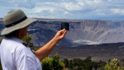 A visitor at Hawaii Volcanoes National Park gets a photo of the expansive crater at Kilauea Caldera. Photography by Baron Sekiya | Hawaii 24/7