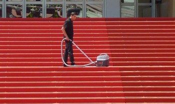 man cleaning red carpet on steps