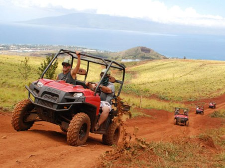 ATV riding through the mountains of Maui with the pacific ocean in the background.