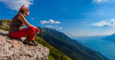 Hawaii Ecotourism - Woman sitting high on Hawaii mountain breathing clean air and feeling the sun