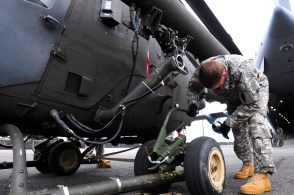 Warrant Officer Justin Garner, a pilot assigned to Troop B, 2nd Squadron, 6th Cavalry Regiment, 25th Combat Aviation Brigade jacks up the left wheel in preparation for loading an OH-58D Kiowa Warrior tail first in the back of an Air Force C-17 Globemaster III during a static load training session on Joint Base Pearl Harbor-Hickam, Hawaii, June 7.