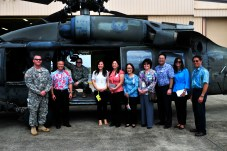 Medical personnel and coordinators with the Queen's Medical Center stop for a group photo with Soldiers assigned to Company C, 3rd Battalion, 25th Aviation Regiment, 25th Combat Aviation Brigade, during a visit to the 25th CAB, 25th Infantry Division to learn about the Army's risk management process for its pilots on Wheeler Army Airfield, Hawaii, June 12.