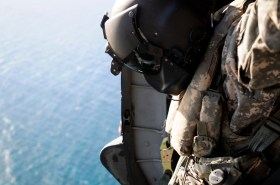 Sergeant First Class Darrell Williams, a UH-60 crew chief assigned to Company B, 2nd Battalion, 25th Aviation Regiment, 25th Combat Aviation Brigade, observes Navy divers with the U.S. Navy SEAL Delivery Vehicle Team 1, Naval Special Warfare Group 3 on the Special Patrol Insertion and Extraction rope during SPIE training with flight crews from the 25th CAB at Marine Corps Air Station Kaneohe Bay June 18.