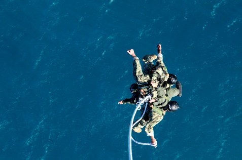 Navy divers with the U.S. Navy SEAL Delivery Vehicle Team 1, Naval Special Warfare Group 3 dangle from the Special Patrol Insertion and Extraction rope attached to an UH-60 Black Hawk assigned to 2nd Battalion, 25th Aviation Regiment, 25th Combat Aviation Brigade during SPIE training with flight crews from the 25th CAB at Marine Corps Air Station Kaneohe Bay June 18.