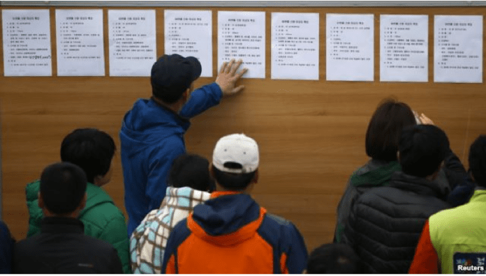 Family members look at a noticeboard with descriptions of bodies recovered from the capsized passenger ship Sewol at the port in Jindo, April 22, 2014.