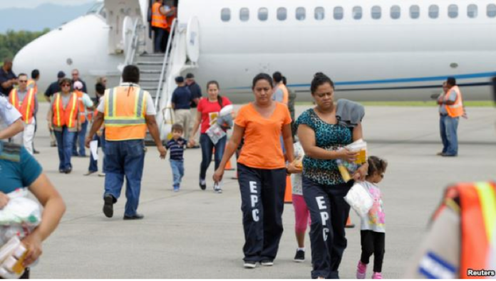 Women and their children walk on the tarmac after being deported from the U.S., at the Ramon Villeda international airport in San Pedro Sula, July 14, 2014.