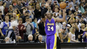 Los Angeles Lakers guard Kobe Bryant (24) holds up the game ball and acknowledges the crowd during an NBA basketball game against the Minnesota Timberwolves after passing Michael Jordan on the NBA all-time scoring list, in Minneapolis, Dec. 14, 2014.