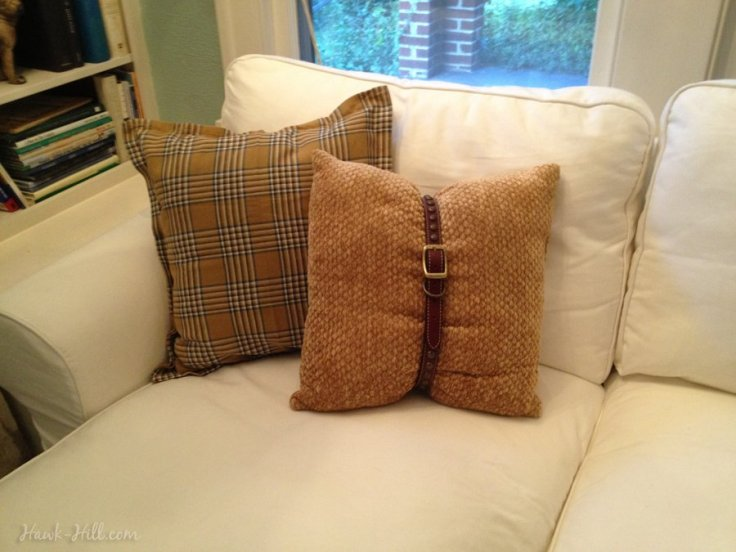 tan throw pillow with brown studded belt