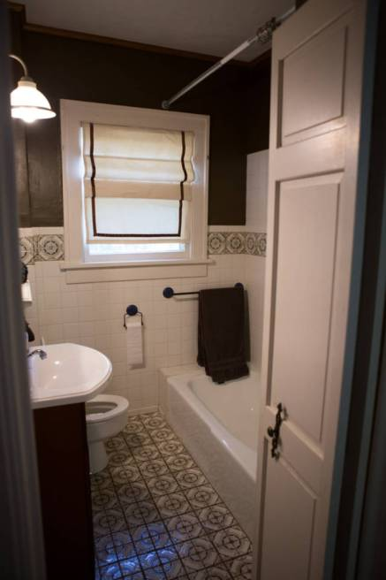 Brown master bathroom with vintage tile work for a 1920's feel
