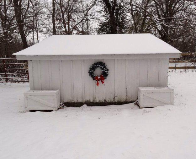 Farm outbuilding in snow with christmas wreath