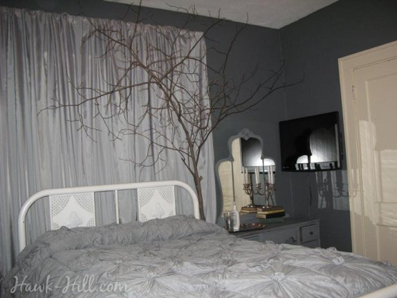 A cozy bedroom with live branches