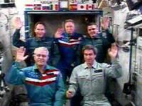 בתמונה: דיירי תחנת החלל הבינלאומית מנופפים בידיהם למכובדי רוסיה שדיברו איתם בועידת וידאו. צילום: הטלוויזיה של נאס''א