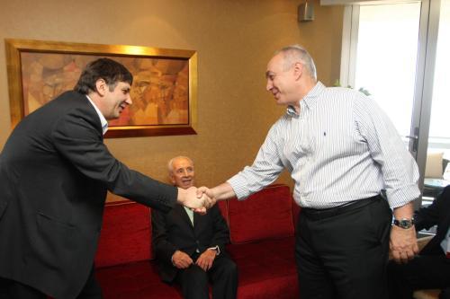 """תצלום משנת 2010: חמי פרס לוחץ את ידיו של חתן פרס נובל אנדרה גיים, וברקע - נשיא המדינה דאז, שמעון פרס ז""""ל. צילום: אילן לוי"""