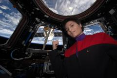 """מהנדסת הטיסה סמנתה Cristoforetti מסוכנות החלל האירופית במדים של סדרת מסע בין כוכבים על רקע החללית דראגון של SpaceX הגיעה לתחנת החלל הבינלאומית ב -17 באפריל, 2015 מלאה באספקה. צילום: נאס""""א."""