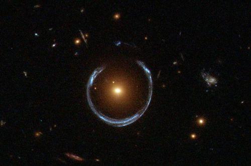 """""""טבעת אינשטיין"""", כפי שצילם טלסקופ החלל האבל, היא תופעה של עידוש כבידתי. כאשר מסה מאסיבית עוברת בציר אחד בין גרם שמיים מרוחק יותר ובין כדור הארץ, קרני האור של הגרם המרוחק יותר מתעקמות סביב המסה המאסיבית ויוצרות מבחינת הצופה בכדור הארץ טבעת שמכונה """"טבעת אינשטיין"""". בחינת שינויים קלים בעידוש הכבידתי תאפשר איתור כוכבי לכת סביב כוכב שיוצר עידוש כזה. מקור: נאס""""א."""