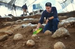כפיר ארביב, מנהל החפירה מטעם רשות מהעתיקות, מנקה את אחת מאבני הקלע באתר החפירה במגרש הרוסים בו התגלה המקום ממנו צרו הרומאים על ירושלים. צילום: יולי שוורץ, באדיבות רשות העתיקות