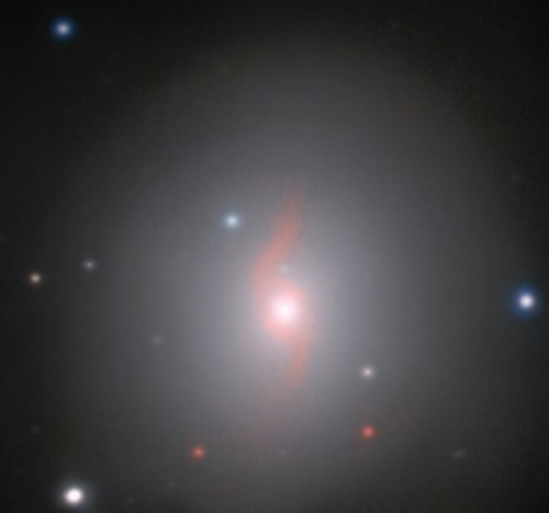"""גלקסיית NGC 4993 המרוחקת 130 מיליון שנות אור מכדור הארץ. ניתן לזהות את ה""""חתימה האופטית"""" של הקילונובה משמאל למרכז הגלקסיה. התמונה צולמה באמצעות מיכשור MUSE (ספקטרוסקופיה מרובת עצמים) ב""""טלסקופ הגדול מאוד"""" של איס""""ו הממוקם במצפה הכוכבים פאראנאל בצ'ילה. מקור: ESO/J.D. Lyman, A.J. Levan, N.R. Tanvir."""