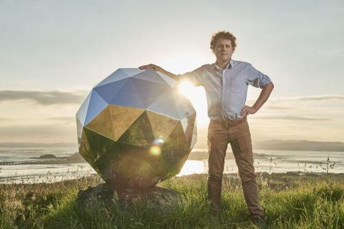 """מייסד ומנכ""""ל רוקט לאב, פיטר בק, עם הלוויין המנצנץ שפיתח. מקור: Rocket Lab."""