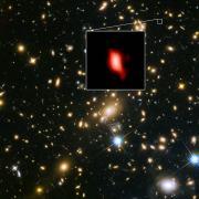 תמונה זו מראה את מקבץ הגלקסיות MACS J1149.5 + 2223 שצולם באמצעות טלסקופ החלל 'האבל' של NASA / ESA. התמונה בריבוע ההגדלה היא הגלקסיה הרחוקה MACS1149-JD1, כפי שנראתה לפני 13.3 מיליארד שנים ונצפתה לאחרונה על ידי 'אלמה'. ריכוז החמצן שגילה 'אלמה' מתואר בצבע אדום. צילום: ESO
