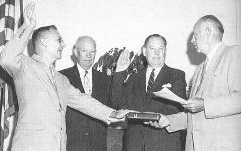 דריידן (משמאל) וגלנאן (שני מימין) מושבעים לתפקידם כשהנשיא אייזנהאור מתבונן (שני משמאל). צילום נאס:א