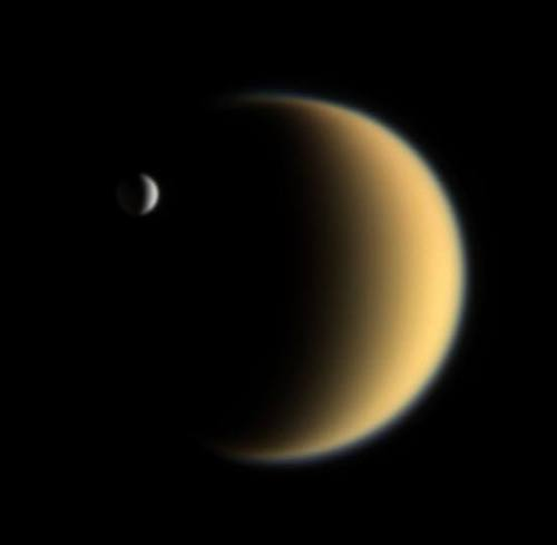 """הירח אנקדלוס והירח טיטאן מופיעים יחדיו בצילום של החללית קאסיני, 2006. כפי שניתן לראות, אנקלדוס הוא ירח קטן מאד, עם קוטר של כ-500 ק""""מ בלבד. מקור: NASA/JPL/Space Science Institute."""