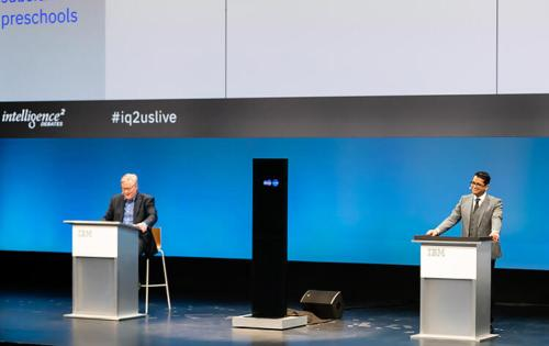 "Project Debater בויכוח מול אלוף העולם בויכוחים, האריש נאטאראג'ן. משמאל, מנחה האירוע, ג'ון דונובן. צילום יח""צ"