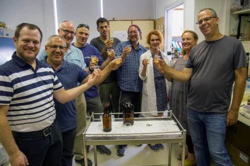 החוקרים ששיחזרו במעבדה את הבירה הפלישתית שותים ממנה. צילום: יניב ברמן, רשות העתיקות