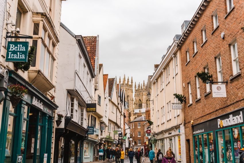 Looking towards York Minster on a crowded shopping street in York, England