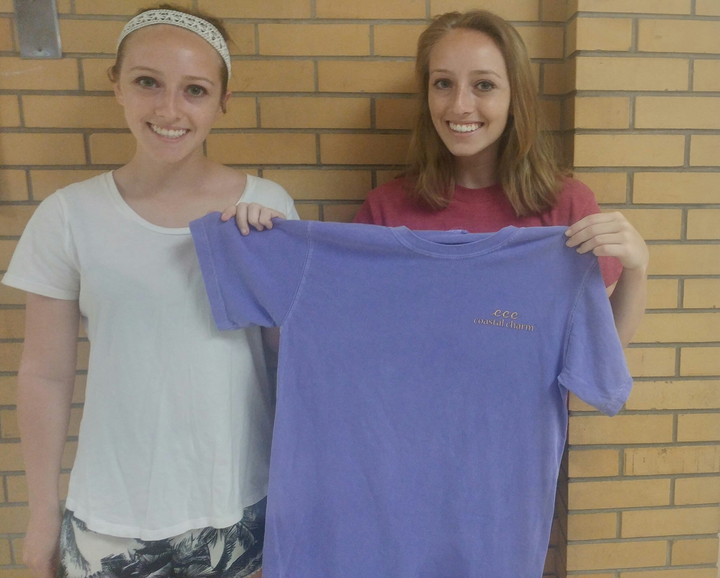 The sisters display their first t-shirt from the brand that features a sea-inspired logo.