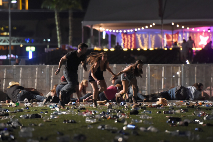 Music festival attendees run and take cover after hearing shots fired into the crowd on Oct. 1 when Stephen Paddock, 64, opened fire on the concert attendees; no motive has been found.