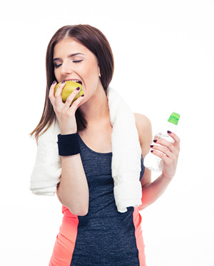 Woman eating a fruit after exercise