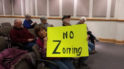 "Margaret Eggers, who was holding this ""No Zoning"" sign in the front row, lives on the western end of the ETJ. ""I am of the opinion that people who want protections could form a property owner's association or do what Valle Crucis did and become a historical district. Don't expect government to do what you can do yourself."""