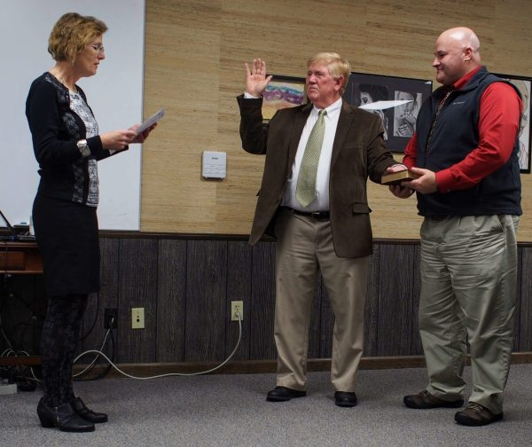 N.C. District Judge Rebecca Eggers-Gryder swears in returning board member Ron Henries, assisted by board member Jason Cornett. Henries would later be voted board chairman.