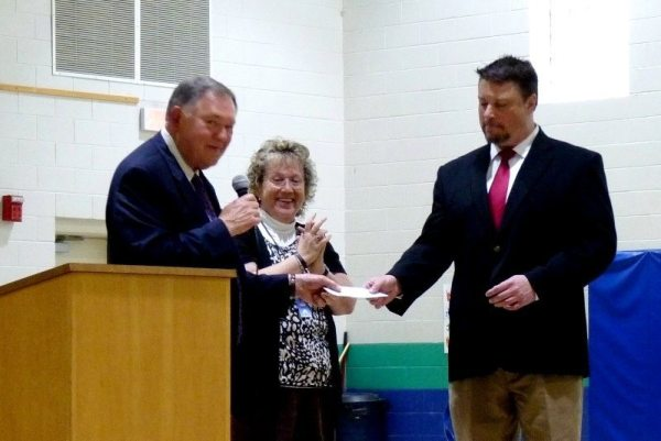 Rufus Edmisten hands the check to Mark Hagaman  as a delighted Patricia Sperry looks on