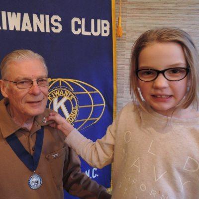 Sadie Grace Barinowski pins the Kiwanis Zeller award on her grandfather, Bob Barinowski