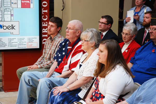 Sonny Sweet (second from left), sitting with family, listens to folks praising him for his service to this country and service to this community.
