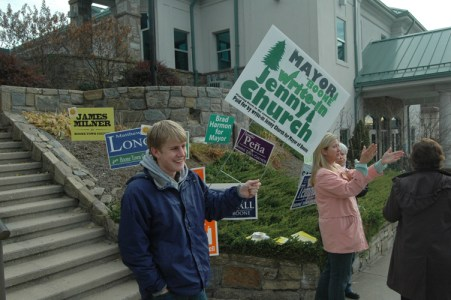 A young man holds a sign touting Jenny Church, a write-in candidate for mayor of Boone. Photo by Jesse Wood