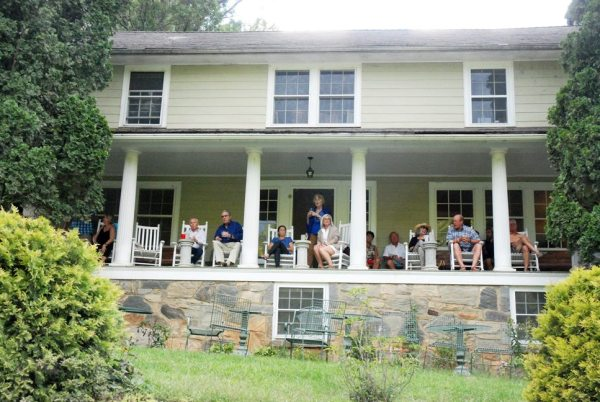 Guests of the River House Inn enjoy the festival environment from the porch.