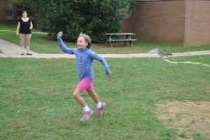 "Hazel Jorgensen shows the spirit of ""ndizotheka"" on the Hardin Park playground. Photo by Emily Rothrock"